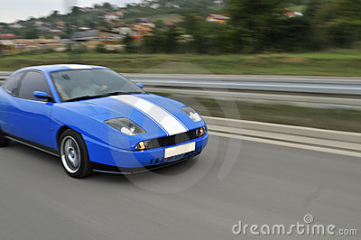 Automobile sportiva veloce blu sulla strada principale