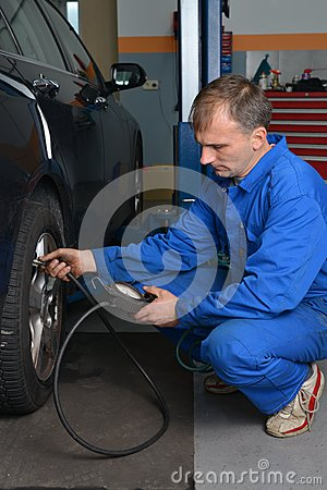 Auto Service Technician Checking Tire Pressure