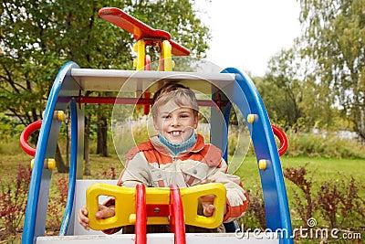 In autumn afternoon, boy plays on playground
