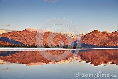 Autumn dawn on mountain lake. Mountains in snow. Kolyma