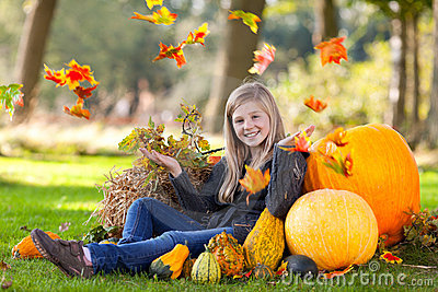 Autumn girl with pumpkin and flying leaves