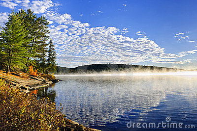 Autumn lake shore with fog