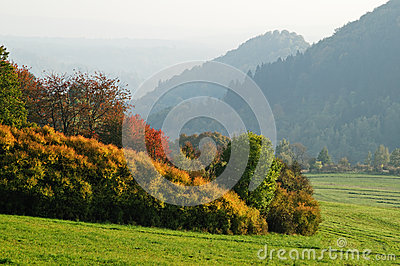 Autumn landscape with mountains in misty haze