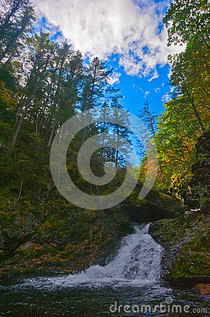 Autumn landscape with a waterfall on the creek taiga.