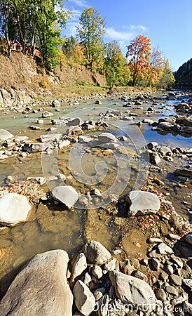 Autumn mountain stony river