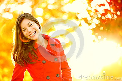 Autumn red trench coat woman in sun flare foliage