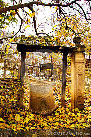 Autumn time: old stone well with yellow leaves