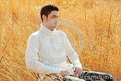 Autumn winter man portrait in outdoor dried grass