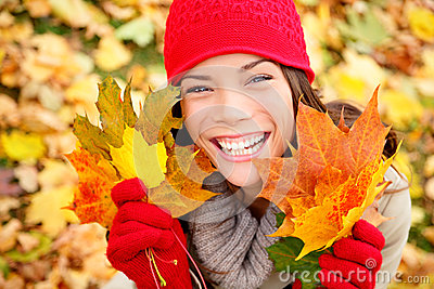 Autumn woman holding fall leaves in forest