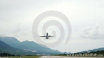 Avión despegado de la pista en el aeropuerto de Tivat en Montenegro. Cielo nublado, montañas almacen de video