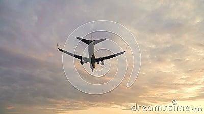 Avión volando sobre el cielo nublado del atardecer. Aviones aterrizando a lentitud nocturna almacen de metraje de vídeo