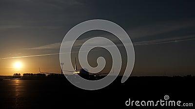 Aviones en pista en la puesta del sol en el campo de aviación sacar y prepararse al vuelo metrajes