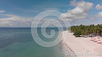 Aviso cinematográfico de drones de playa vacía de arena blanca con paraguas rojos y mar azul o océano limpio y tranquilo con bote almacen de metraje de vídeo