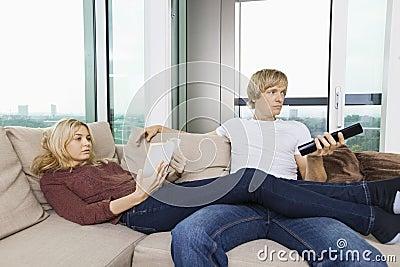 Avkopplad parläsebok och hållande ögonen på TV i vardagsrum hemma