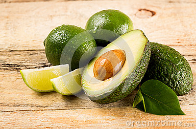 Avocado and limes on wooden background