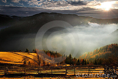 An awesome mountain landscape with sun, fog, and f