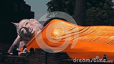 Ayutthaya Thailand - April 5, 2019: Handelsresande bekläs med den gula ämbetsdräkten av den buddha statyn i den Wat Yai Chaimo stock video