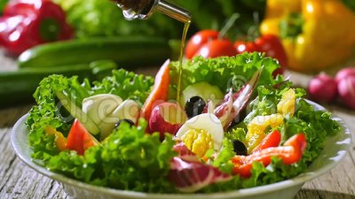 Azeite que derrama sobre salada misturada