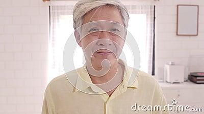 Aziatische bejaarden voelen zich gelukkig glimlachend en kijkend naar camera terwijl ze ontspannen op de bank in de woonkamer thu stock footage