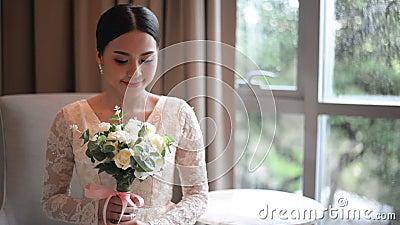Aziatische bruid in de holding van de kantkleding en van het geur mooie witte huwelijk bloemen stock videobeelden