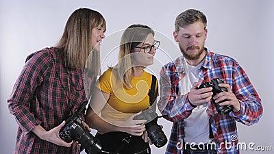 Azienda di professionisti con fotocamere digitali che studiano le immagini scattate in studio durante il seminario per archivi video