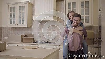 Bärtiger Mann trägt die hübsche Frau, die zurück auf seiner in der Küche sitzt Frau umarmt Ehemann und zeigt ihm Richtung mit ihr stock footage