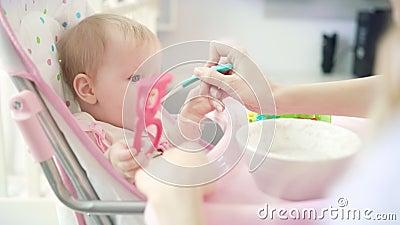 Bébé avec le jouet se reposant dans la chaise et mangeant de la purée Chéri alimentante de mère avec la cuillère banque de vidéos