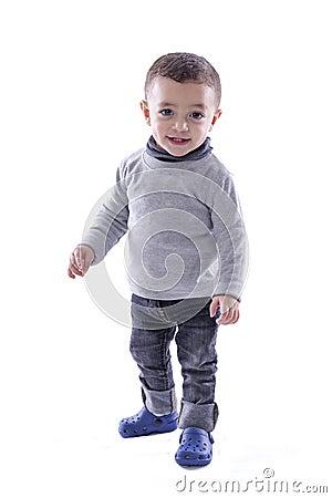 Bébé garçon joyeux se tenant au-dessus du blanc