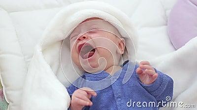Bébé garçon pleurant nouveau-né L'enfant nouveau-né a fatigué et affamé dans le lit sous un bleu a tricoté la couverture banque de vidéos
