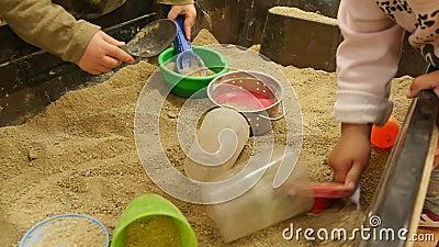 Bébés jouant avec le sable dans le jardin d'enfants Childcare banque de vidéos