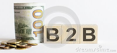 B2B written on a wooden cube with coins and dollars. B2B written on wooden cube with coins and dollars stock image