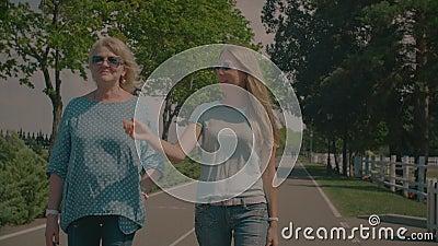 Babbelende hogere moeder en volwassen dochter die in park lopen stock video