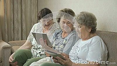 Babcie patrzeją fotografie używać cyfrowe pastylki zdjęcie wideo