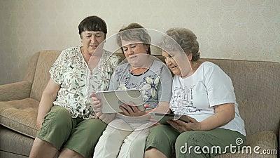 Babcie patrzeją fotografie używać cyfrowe pastylki zbiory wideo