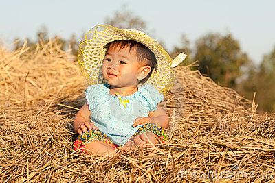Baby of Asia sits on straw