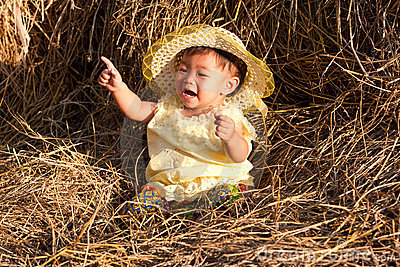 Baby of Asia sits in straw