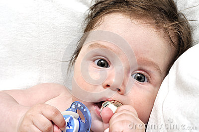Baby in bed with dummy and silver toy