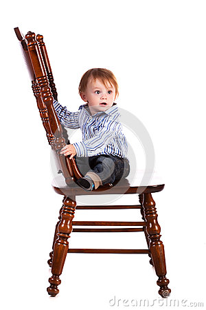 Baby on a big wooden chair in a studio. isolated