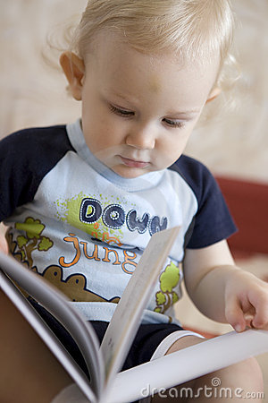 Baby blond boy with book indoors