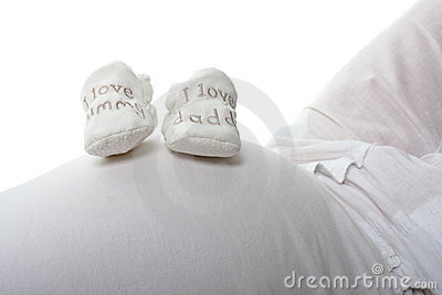 Baby booties on expectant mothers bump