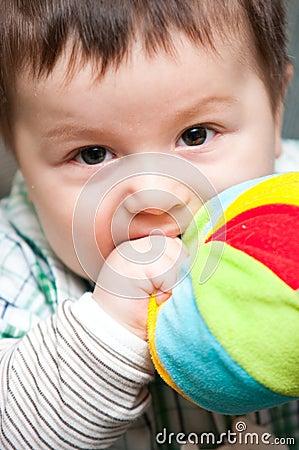 Baby boy bites toy