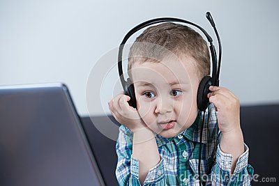 Baby boy with headphones at the computer