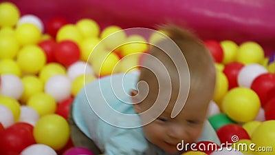Baby boy in het zwembad met ballen in het amusementscentrum van kinderen Langzame beweging stock footage