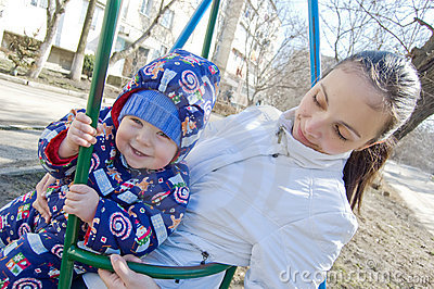 Baby boy and his mother on swing