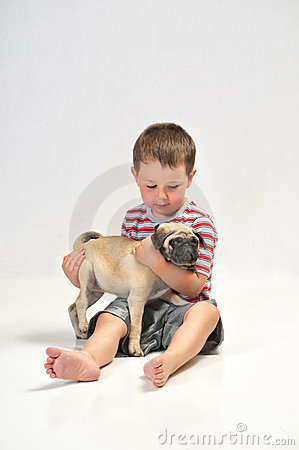 Baby boy holding a Pug