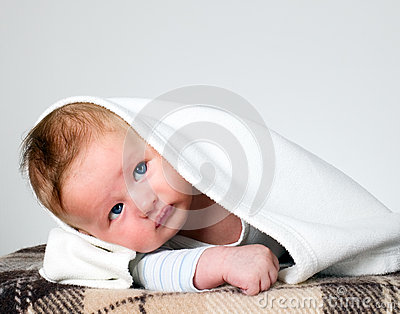 Baby boy holds raised head with blanket over head