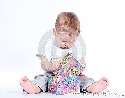 Baby boy opening gift box on white