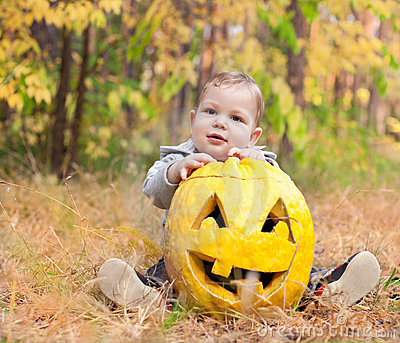Baby boy outdoors with real pumpkin