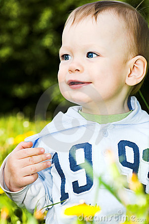 Baby boy play with dandelions