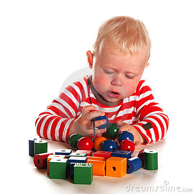 Baby boy is playing with wooden beads